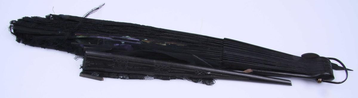Av sort chiffon og maskinvevd blonde, en halvdel av hver, sydd sammen i spileretningen. Lisse i kanten. Spilene er av sortmalt tre med innpresset mønster av sirkler og stiliserte ranker på forsiden. Annenhver spile har også gjennombrutte striper. På viftehalvdelen av chiffon er det malt naturalistiske stemorsblomster og blader. Metallhempe.