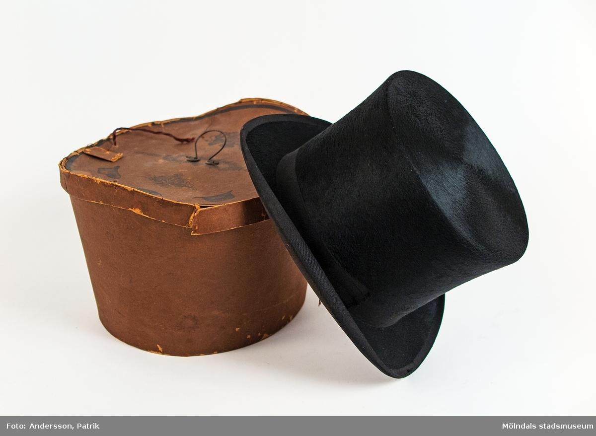 Brun oval, konisk hattask med lock och liten stålögla som handtag. Innehåller en svart stormhatt, dvs en hög herrhatt med platt ovandel samt ovalt, styvt och sidouppvikt brätte. Användes vid högtidliga tillfällen.Hattens mått: H:155 mm, L:300 mm, Br: 230 mm.Hatten märkt inuti med två A:n (Axel Andersson-Tidefors som var givarens far.)