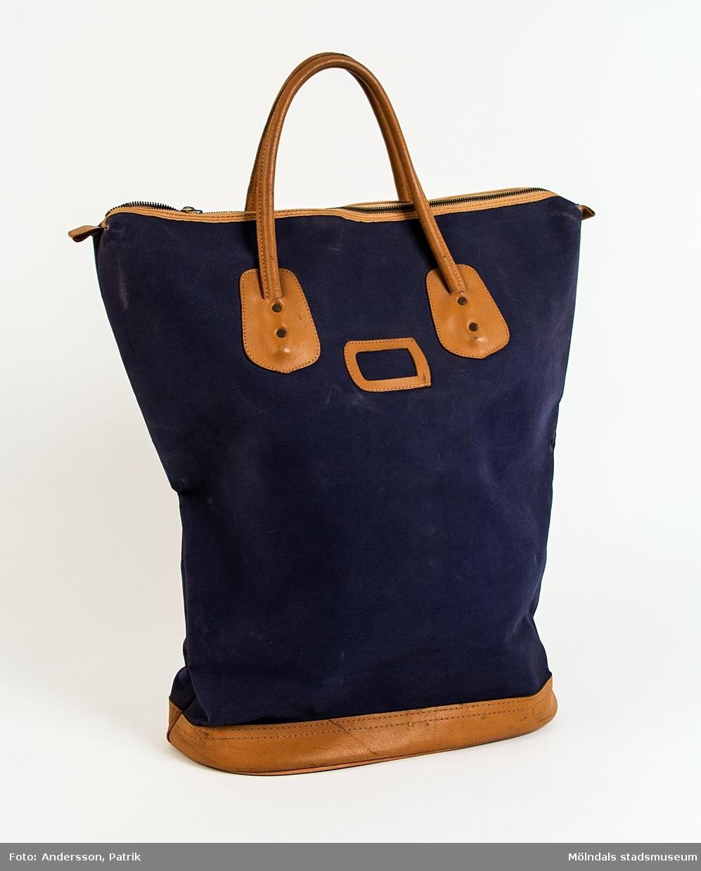 Väska i blå canvas och med bruna skinndetaljer, från cirka 1950 - 60-talet.  Väskan har en dragkedja och två handtag i skinn. På väskans ena långsida finns plats för en etikett, exempel namnetikett.