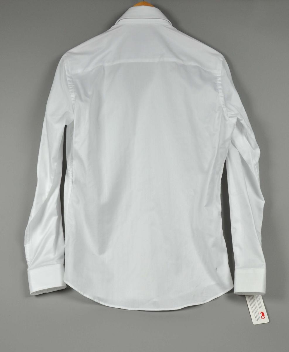 """Hvit skjorte ,knappene har påtrykt; """"moods of norway"""".På brystlommen er det påbrodert """"traktorlog"""" og en rød og blå loddrett stripe i ytterkant ved søm. Str.:S"""