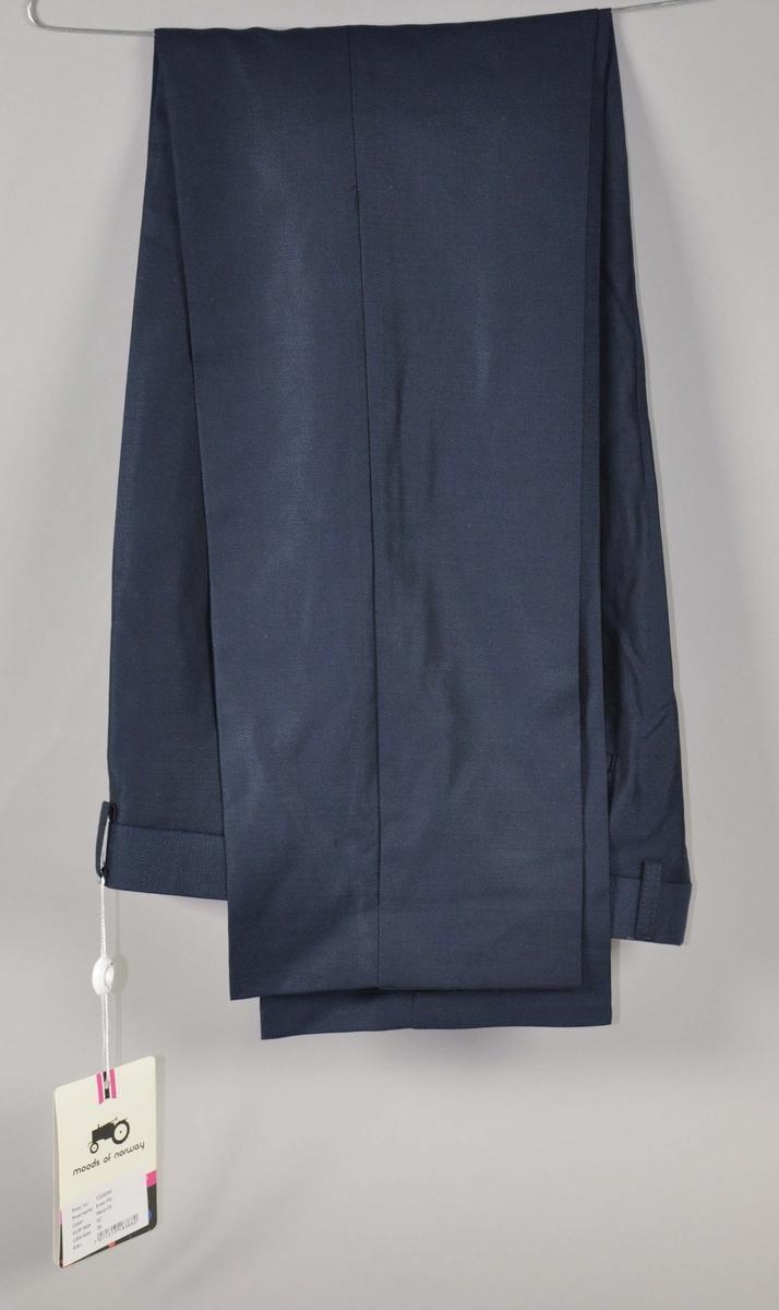 """Mørkeblå ull/silke herrebukse med to stikklommer og to baklommer med knapper. Hvit """"traktor-logo"""" brodert over høyre baklomme.Linningen foret med stripete bomullsstoff , påbrodert  """"Heia Norge"""" syv ganger. Str.52"""
