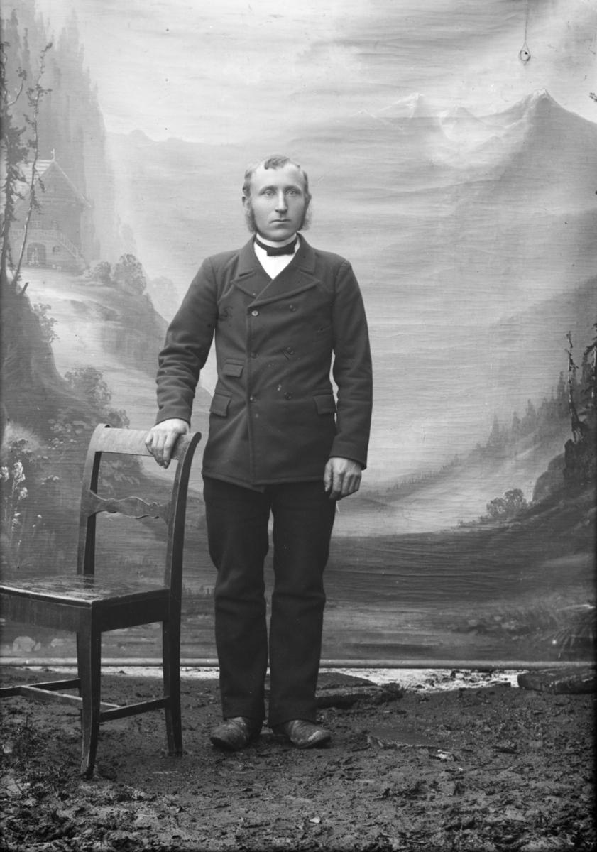 Portrett, mann står ved stol, helfigur. Petter Brunhaugen