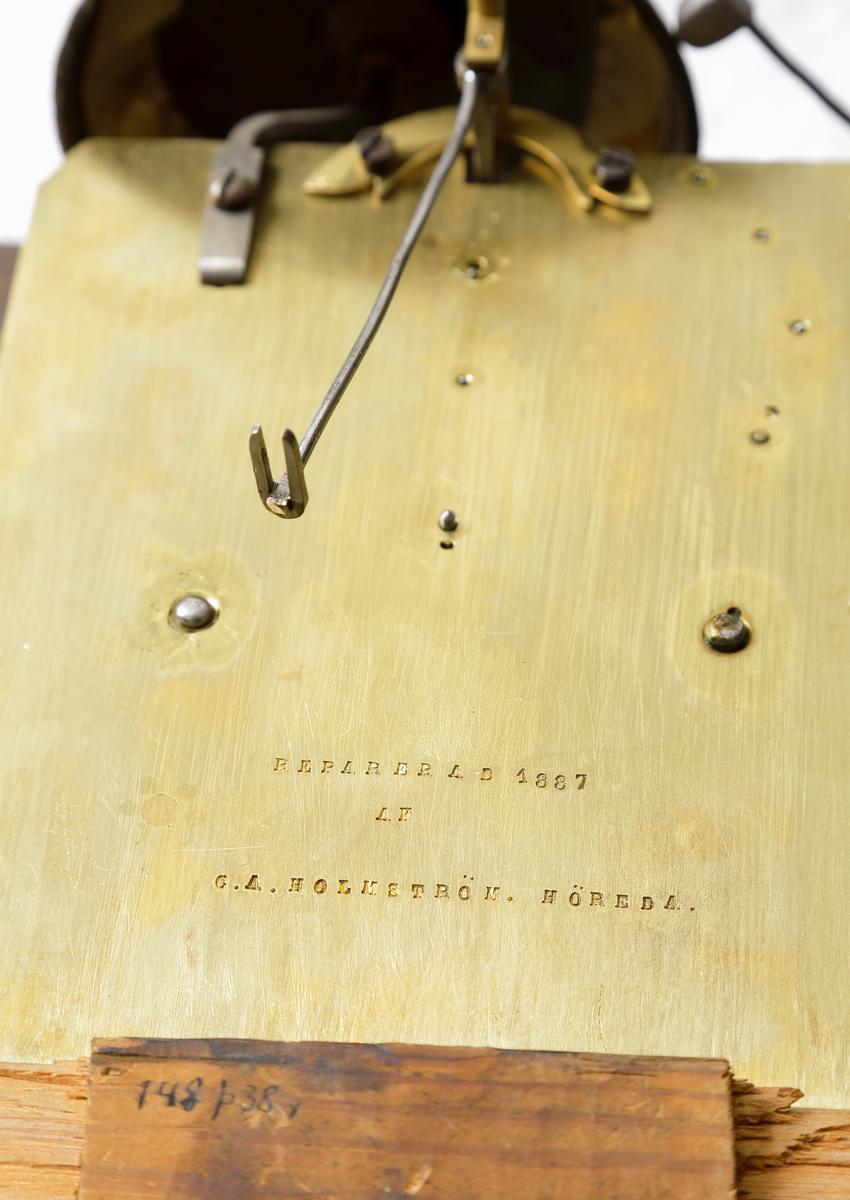 """Golvur s.k. ståndur.  Rakt, rektangulärt fodral av alm (?). Står på fyra tillplattade kulfötter av svärtat trä. Huv med glaspartier och urtavla av tenn med romerska siffror och text: """"Modeweg Brandsbo"""", omgiven av trekantiga fält med förgyllda partier i relief.  Uret är försett med en vev för loden och en nyckel för uppdragning."""