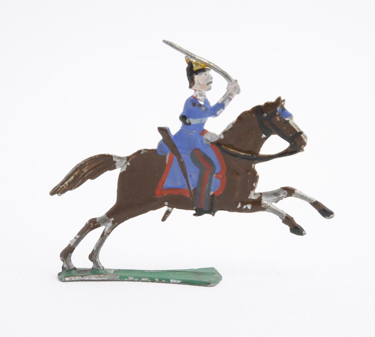 Ryttare i blå uniform, med koppel och pickelhuva, sittande till häst.