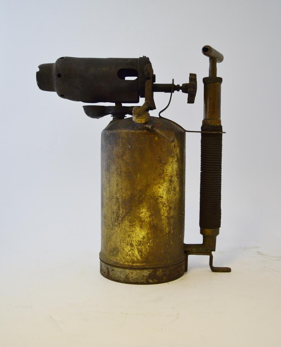 Sylindrisk beholder med brenner på toppen. Håndtak med pumpe festet til beholderens rygg.