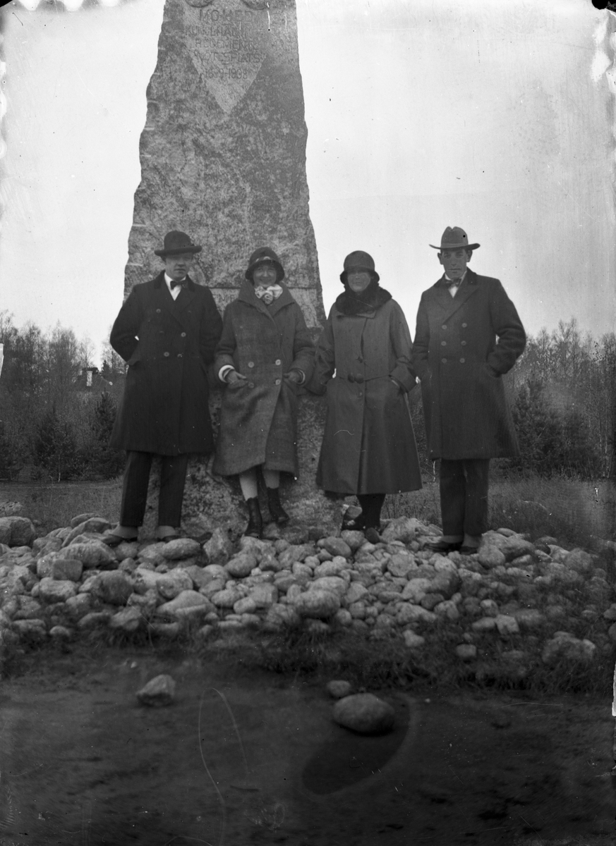 Fyra personer vid Mohed regementes monument (sten).