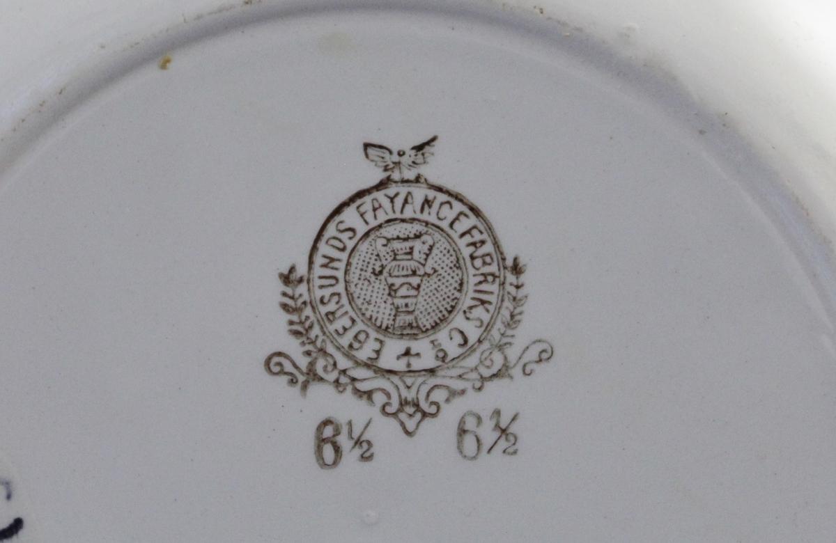 Rund tallerken med hvit bunn med dyremotiv. En dekor i speilet i form av en hare, seks dyremotiv i form av høner og haner på fane. Motiver i flere klare farger.
