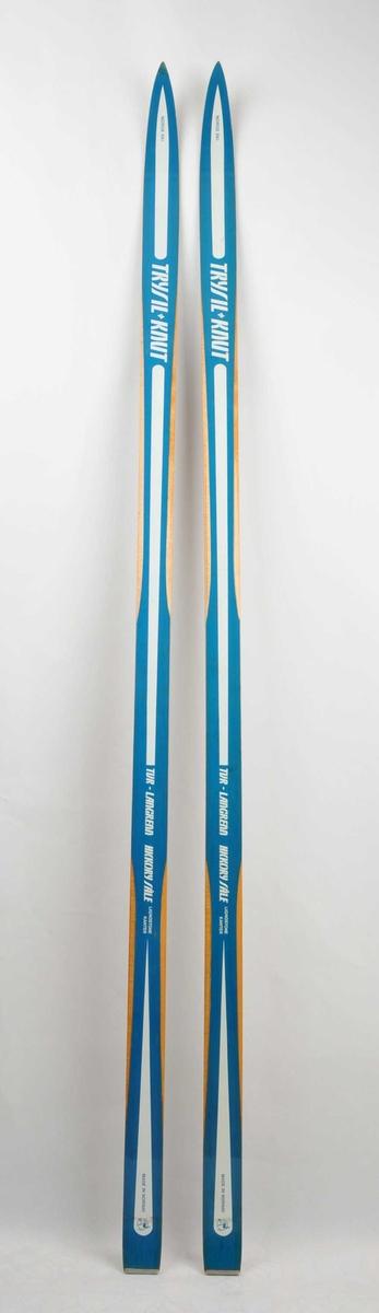 Langrennski laga av tre. Lakkera, med blå overside, kvit dekor, trekvite sidekantar. TRYSIL-KNUT er skrive med store kvite bokstavar. Emblem med ein skilaupar nede på skia. Metallbeslag på baktupp