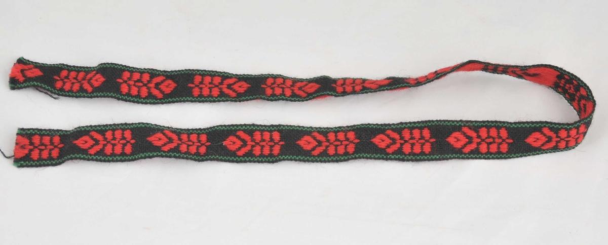 Håndvevd på bandvev i svart, rødt og grønt. (Kan vera ein prøvelapp).