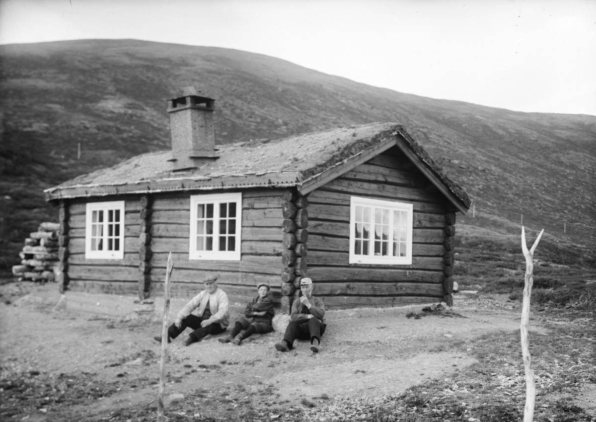 Tømmerhytte på fjellet, to menn og en gutt sitter ved hytteveggen