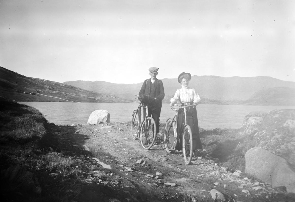 Mann og kvinne med sykkel ved fjellvann. Antatt Sjodalen