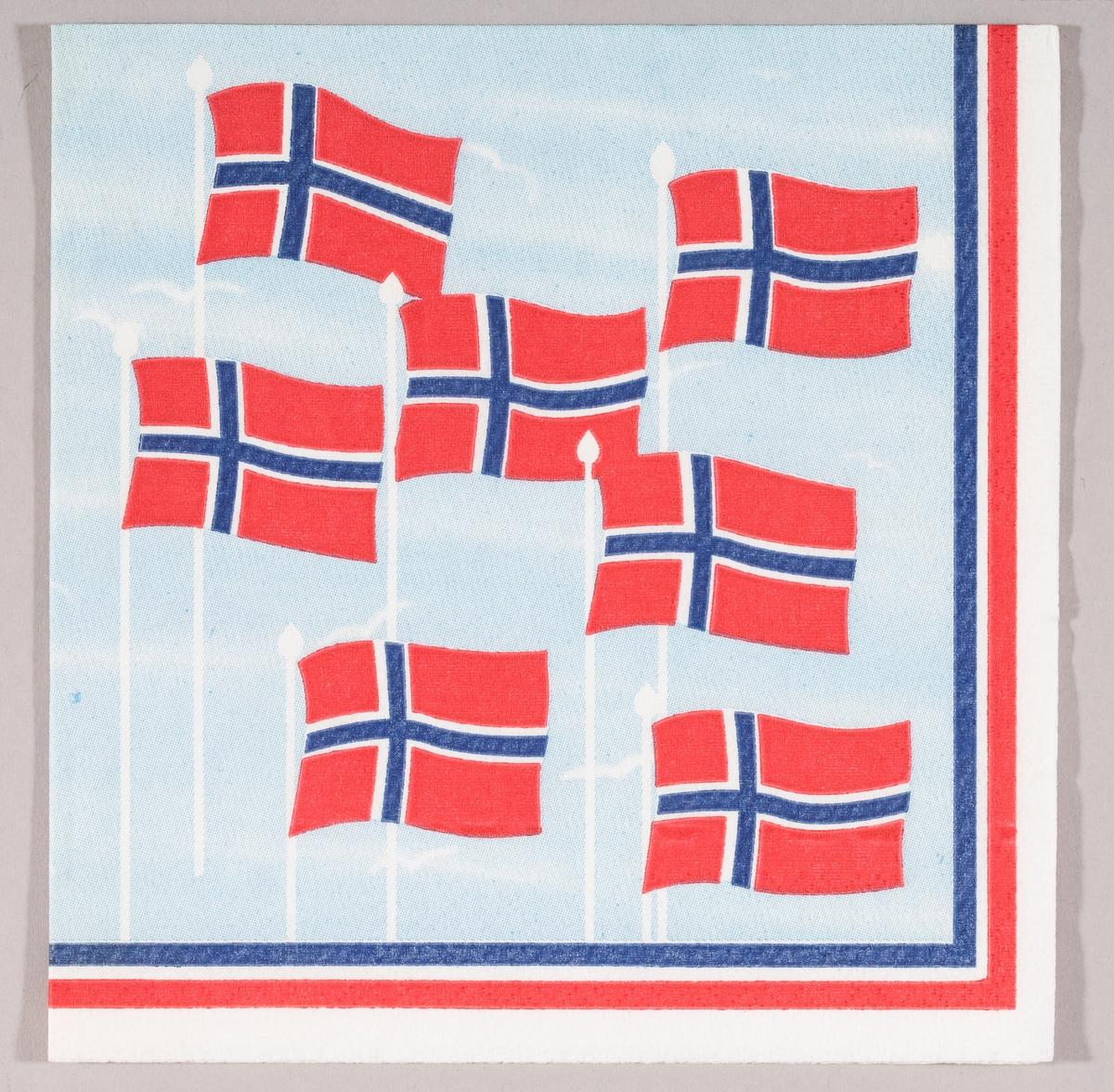 Norske flagg som flagrer i vinden mot en lysblå himmel