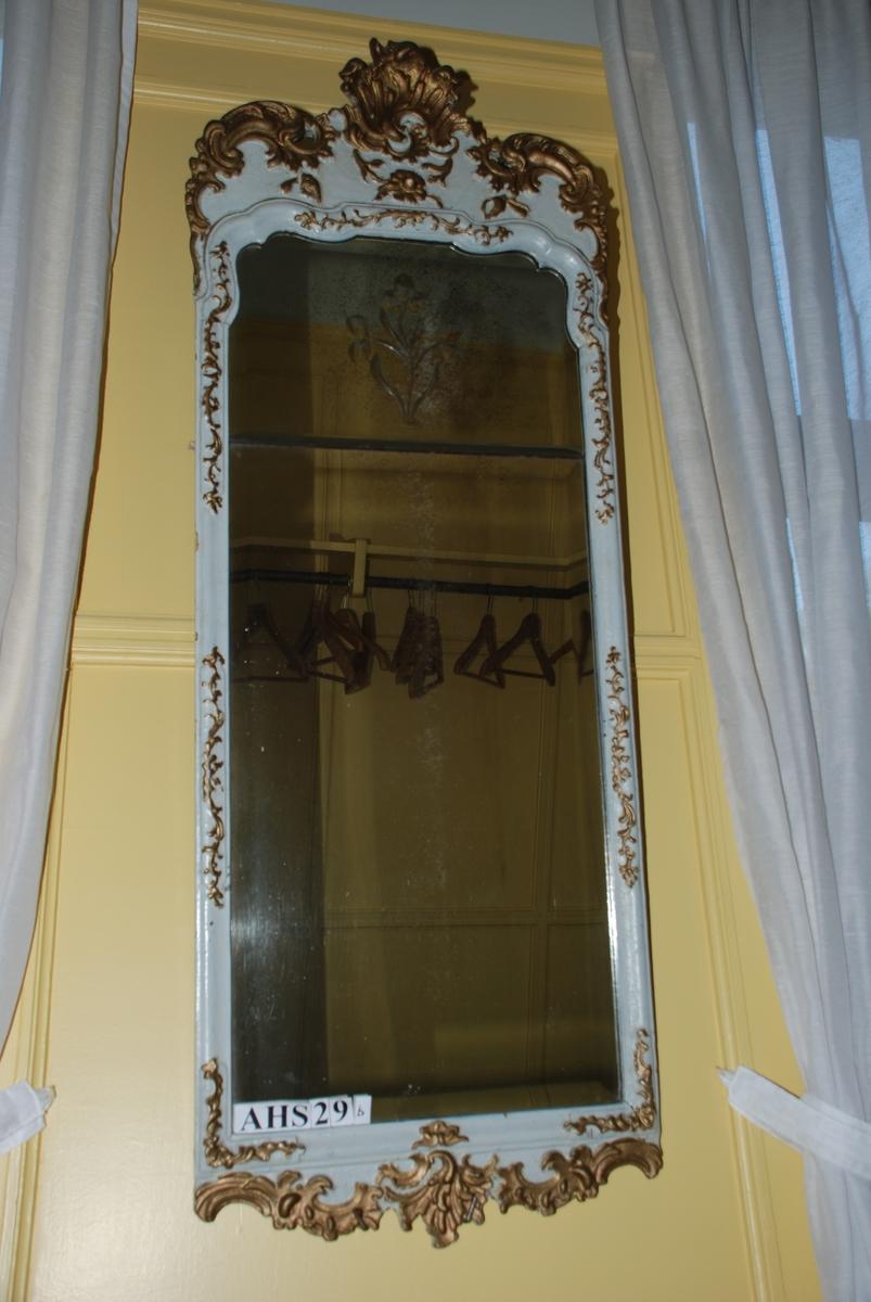 Rokokko. Hvitt og gull. Speilets glass er delt i to. Øverste felt prydet med en glassblomst i veneziansk manér. Chippendale-rokokko-type. Forgylte, skårete rocailler både nede langs kanten, oppover langs sidene, særlig på overdelen.