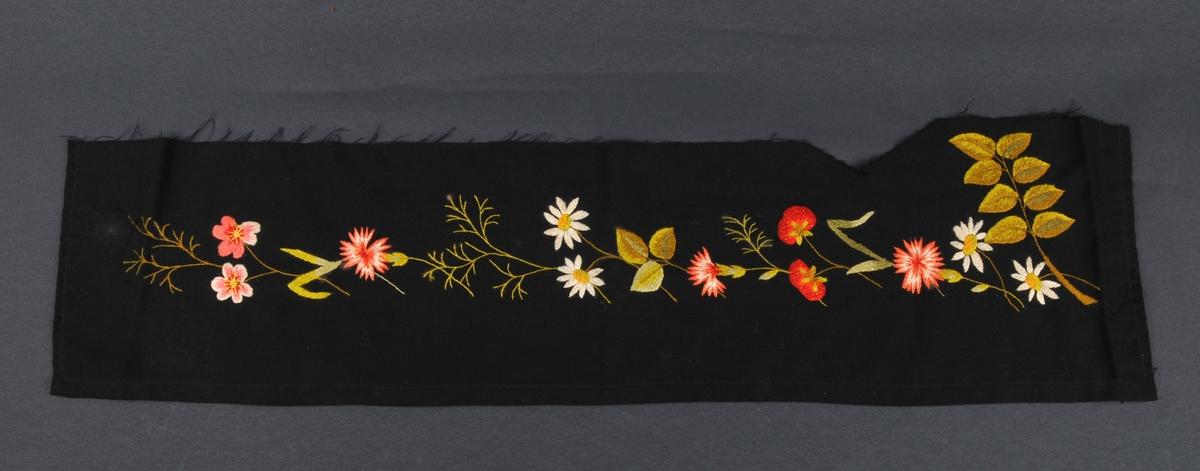 Broderi på svart ullstoff, nedre del av eit draktforkle. Motivet er naturalistiske blomar, markjordbær og bladverk.
