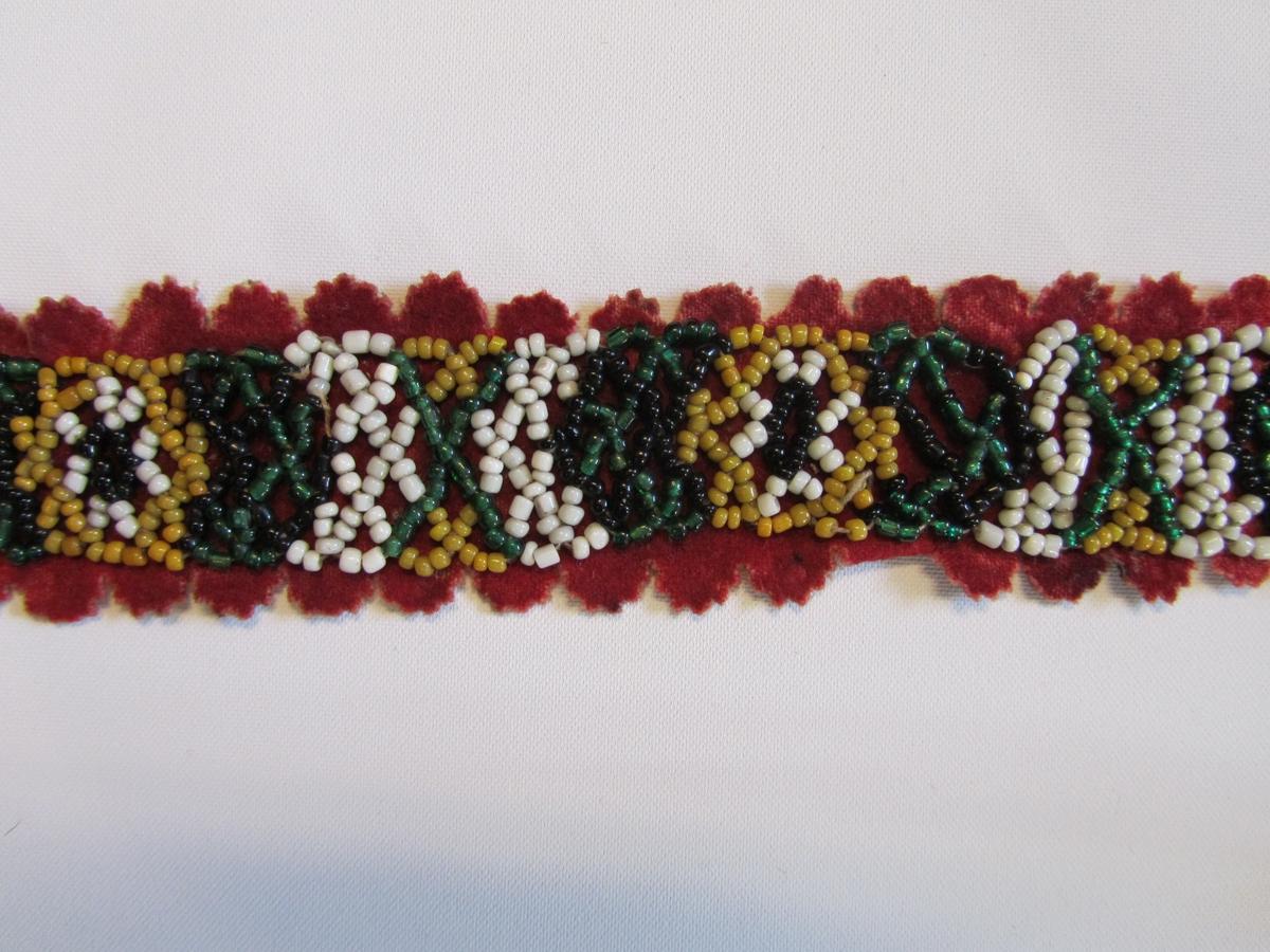 Belte med botn av rødt klede. Tredd band av småperler i forskjellige farger er påsydd. Langsidene og eine enden har utstansa, taggekant med halvsirkler  ca 1 cm i diameter. Manglar spenne.