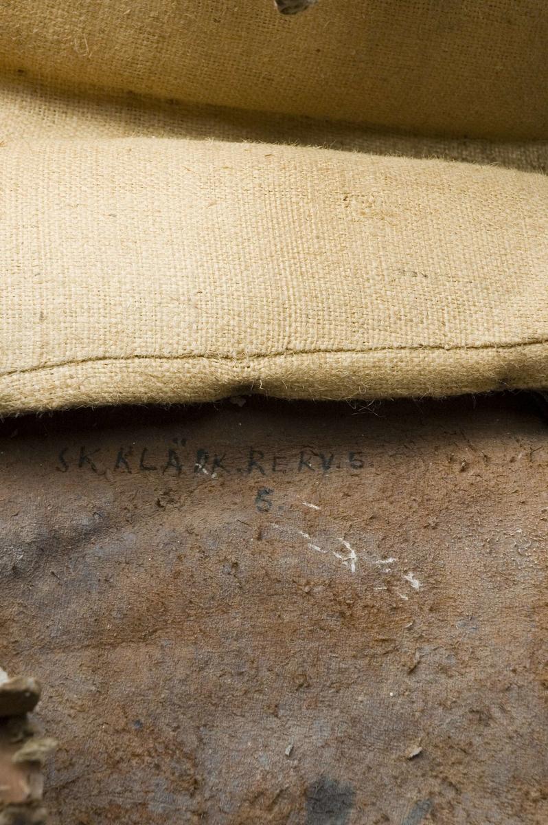 Brudsadel, handgjord. Modell där den ridande färdas sidledes, med fötterna på samma sida på ett fotstöd. Försedd med ryggstöd. Stomme av trä. Sitsen, sido- och ryggstöden stoppade och klädda med grön ylleplysch, nersydd i mönster med röd tråd, troligen av lin. På utsidan är stöden klädda med brunt skinn, plåt och nitar. Både plåt och skinn har genombrutna partier, med underliggande rött kläde. Märkningen GTDR (osäker) samt 1809 är utskuret i plåt med rött kläde under. Detta är placerat på bakre sidostödet. På båda sidorna hänger stycken av läder med rundade hörn, med präglat mönster som liknar en blomsteruppsättning av barocktyp. Fotstödet hänger på vänster sida, i justerbara remmar av läder med söljor av metall. Trästommen är också stoppad ned mot hästryggen, och klädd med säckväv av jute. Det finns också remmar för fastsättning av sadeln, men de är korta och måste skarvas. Allt trä klätt med målad säckväv.