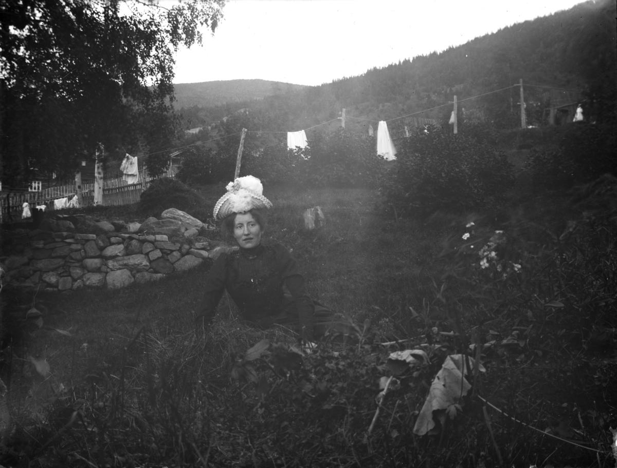 Kvinne med hatt sitter i gresset i hagen