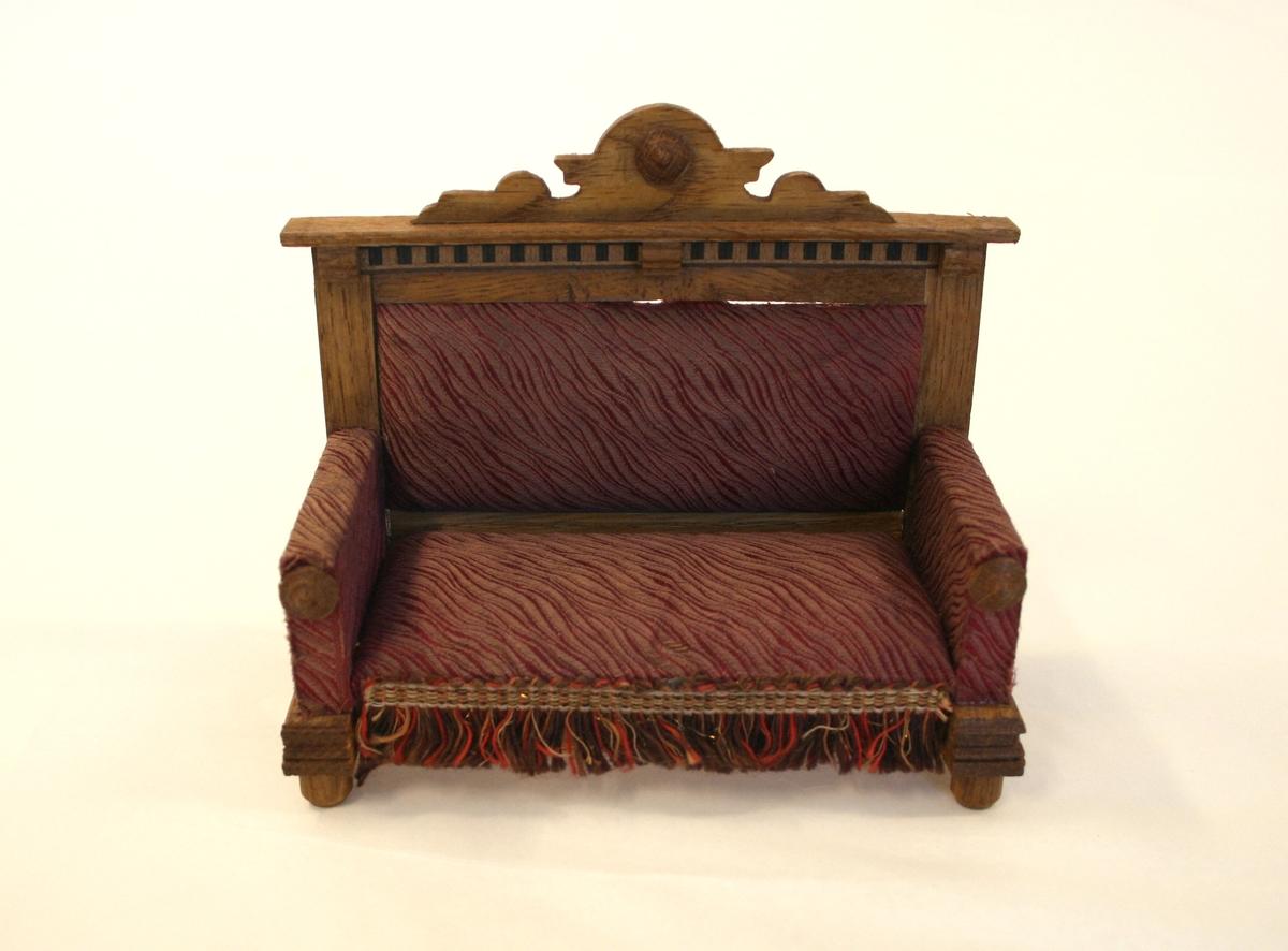 Dukkehusmøblement bestående av 8 deler.  A) Sofa med høy rett rygg med stripete rødt silkestoff på setet, rygg og armlener. Utskjært toppgavl i tre og brune, røde og gule frynser nederst i front.  B) Bord i tre, rektangulært med fire rette ben.  C) 5 stoler, spisestoler. Dreide forben, rett høy rygg med fiolinformet midtstav, løvsagarbeid. Sete i rødt stripete silke med frynser i rødt. brunt og gult i front og på sidene.  D) Skap med dobbeldør og skuff over i tre. Rektangulært speil gavlbekroning over. Metallbeslag på midten av skuffen og to på hver side av skapdørene.