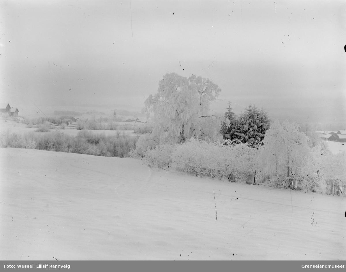 Vinterlandskap, ukjent sted. En kirke kan ses bak i bildet.