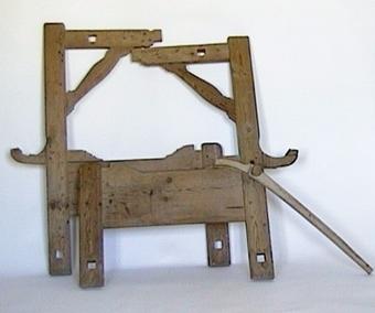 Vävstol av trä. Mellan stolens lodräta benen finns rektangulära trästycken som i ena änden försetts med konkava hållare för trärullen till den färdiga väven. Upptill på två av de längre benen finns hållare av trä, försedda med rektangulära genomgående hål. Diagonalt finns stöd av trä mellan hållarna.