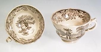 Två koppar av vitt flintgods med tryckt svart landskapsdekoration föreställande vallpojke.