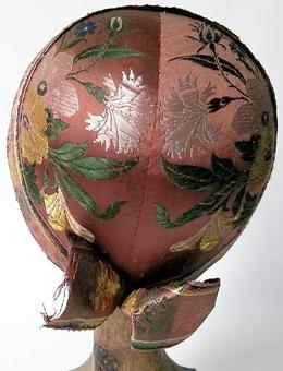 Bindmössa klädd med mönstervävt siden, rosa med blommor. Hjässband av mönstrat siden,avslutat med en rosett i nacken. Fodrad med blå-vitrandigt linne.