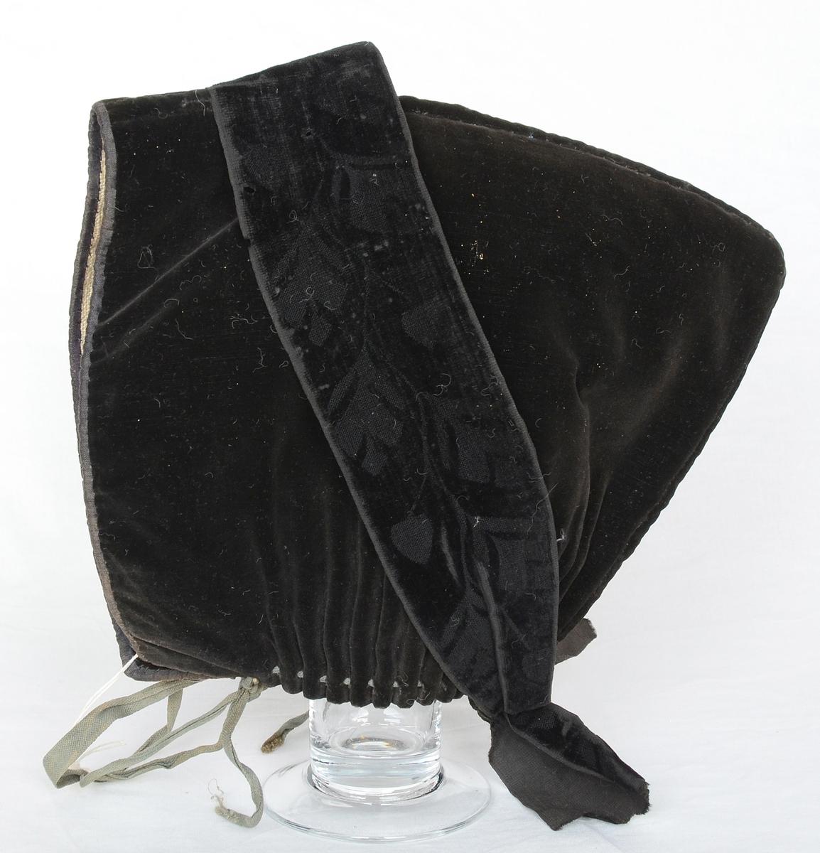 """Krokmössa av svart sammet med linnefoder, veckad i nederkanten med ett band igenomträtt i vecken, bandet långt för knytning. Ett svart sammetsband snett över mössan knytes med en knut i nacken. Till mössan bärs ett rakt stycke så kallad """"knytting"""". Vid kyrkobesök bärs ett broderat stycke och vid sorg bärs ett helt slätt stycke. Alfta och Ovanåker har båda denna kvinnomössa, men den ena socknen har större pik på mössan."""