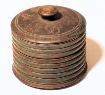 Rund, svarvad ask av trä med trycklock, prydd med utsvarvade band. Målad grönblå, på locket tre målade stiliserade blommor samt initialerna B.J.D.