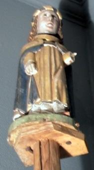 Ljusängel bestående av ängel och ny stav. Ängelns karnation är ljus, håret brunt och huvudbonaden har en virad kant. Mantel och tunika är förgyllda, mantelns huva är svart med guldromber och röd tofs och alban är vit. Ängeln står på en grön marksockel.