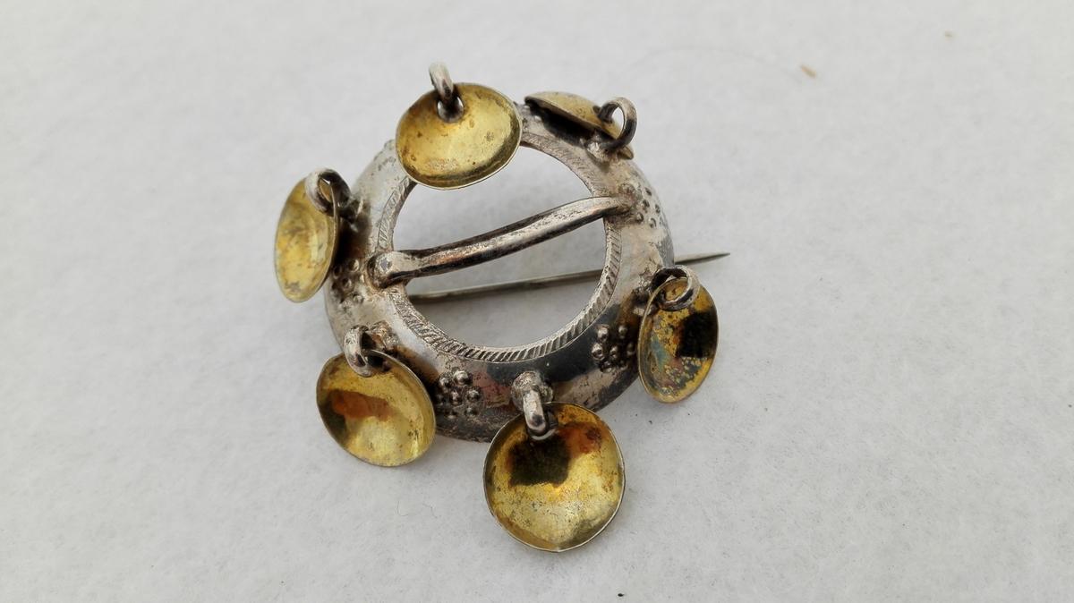 Form: Ringforma. Fastlodda tversoverliggande nål (den opphavlege nål for feste.) Sekundært påsett tynn nål på baksida.6 pålodda hemper m lauv i lik avstand kring ringen. Gylte lauv.