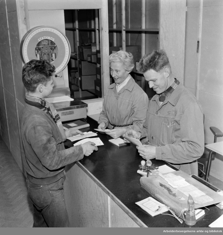 Økern. Godsrutestasjonen. Til venstre står Hans Kopperud fra Jessheim-ruta. Han blir ekspedert av Ingrid Steen og Gustav Eek. Mars 1960