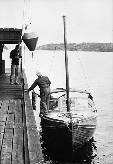 """Enligt uppgift: """"En av forskningsfartyget """"Skageracks"""" utrangerade livbåtar, kallad """"Nyvåg"""", togs till stationen 1961-62. Från början öppen livbåt, ruffades för att användas vid mätningar. På bilden syns från vänster assistent Leif Nyberg och Oscar Åkermo. På bilden används en vattenmätare med boj""""."""