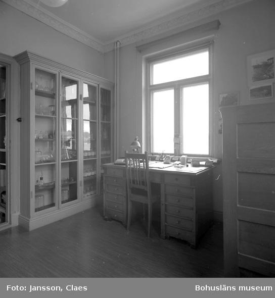 """Enligt uppgift: """"Vågrummet. Till vänster skåp där bl a provglas, blykulor och mätkulor förvarades. Framför fönster ett äldre skrivbord. Vågen förvarades i motsatt hörn i vågrummet""""."""