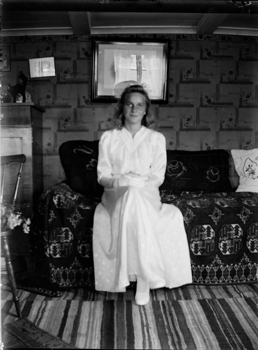 2f6a8a2cfdb9 Flicka i konfirmationskläder sitter i en soffa med vackert täcke och  kuddar. Rummet har lågt