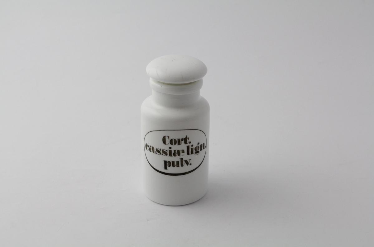 Hvit, rund porselenskrukke med vid hals og slipt propp. Sort påmalt påskrift med oval ring rundt. Brukt til oppbevaring av legemidler/pulver på apotek, nærmere bestemt pulverisert cæssia bark.