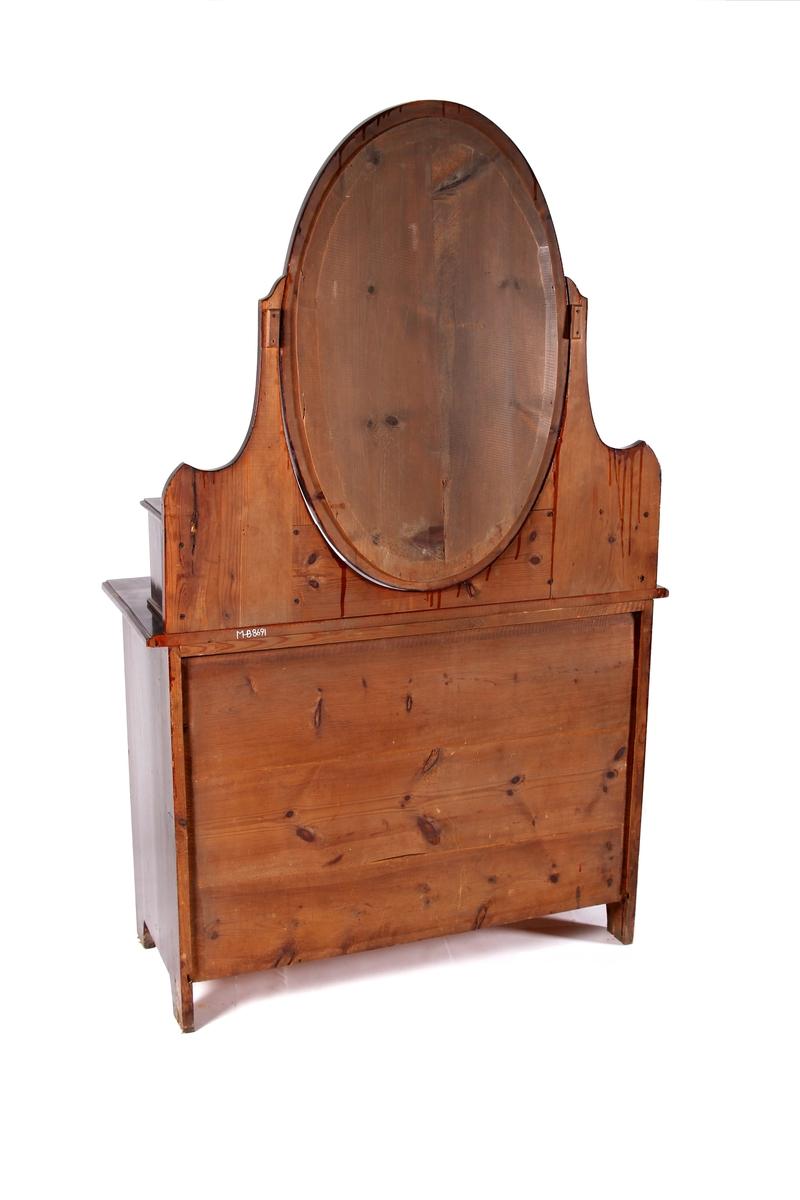 Brunlakkert toalettkommode med oval speilramme. Overdelen består av speil og skuffeseksjon med ti skuffer på hver side. Underdelen består av to langskuffer og to mindre skuffer øverste. Firkantet håndtak med nøkkelskilt i hver skuff.