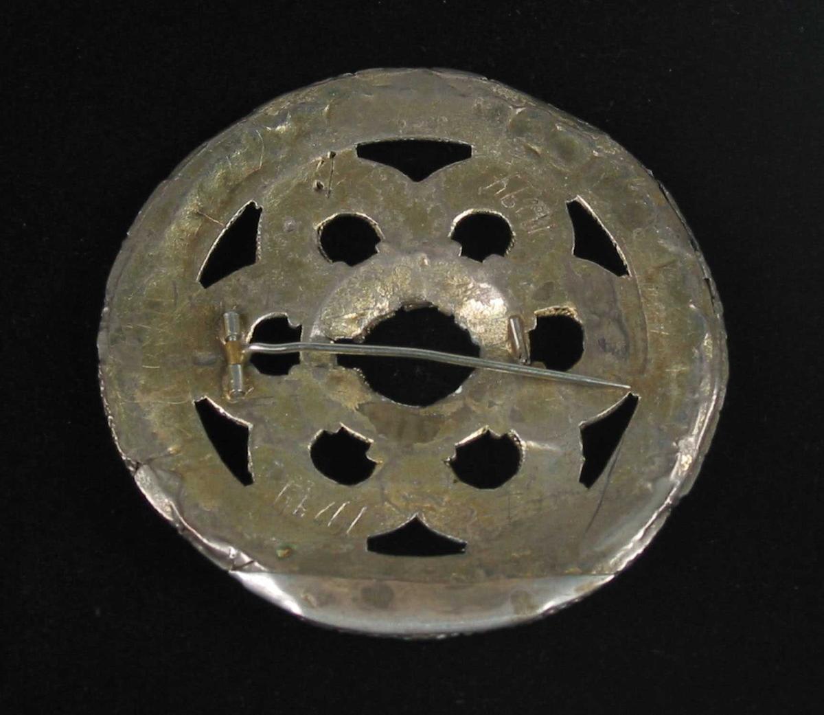 Slangesølje i forgylt sølv. Gjorden er av rørtråd. Tornringen er svært defekt. Tornen er brukket av og erstattet med en påloddet nål på baksiden. Den ytre kruseringen er kantet med flettetrådsbånd mens segmentene er skilt fra den indre ringen med tvinnnetrådsbånd. Dessuten er de seks segmentene kantet med tvinnetråd. På den ytre kruseringen veksler diamantkruse med perlekruse unntatt et enkelt sted der to perlekruser er stilt sammen. Samme veksling finnes på segmentene, men diamantkrusen som står i segmentskillet er sammensatt av tre lag kruser. Det underste laget er åttedelt. På den innerste kruseringen er det pålagt kun perler. Mellom hver eneste kruse er det pålagt en liten perle i ytterkant, på den ytterste kruseringen også i innerkant. Sølja er restaurert og forsterket med en sølvplate på baksiden. Ingen synlige stempler.