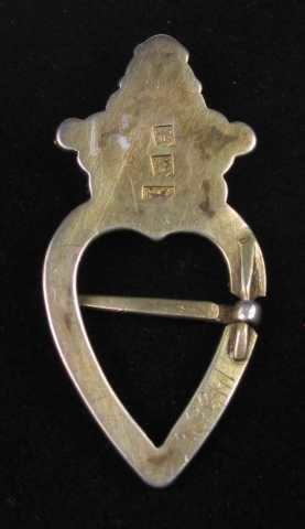 Krusesprette av forgylt sølv med innlagt rød stein. Bunnplata er skåret ut av ett stykke. Både hjertegrinda og krona er belagt med perlekruser. Krona har også perlefyll utad.Tornen er festet på tvers av hjertegrinda.