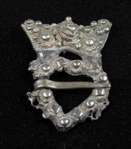 Krusesprette av sølv. På midten har den en tredobbel diamantkruse omgitt av små perler og perlekruser. Langs kanten er det pålagt tvinnetråd. Hjertegrinda er utvendig og innvendig kantet med tvinnetråd. På forsida er den dekket av perlekruser og diamantkruser. Langs kanten har det opprinnelig vært trådløkker.Tornen er skravert og er festet på tvers av hjertegrinda. Krona ser ut til å være forgylt. Krona har vært revet løs fra grinda og er loddet skjevt på igjen. Forsterket på baksida. Ingen synlige stempel. Svært slitt.