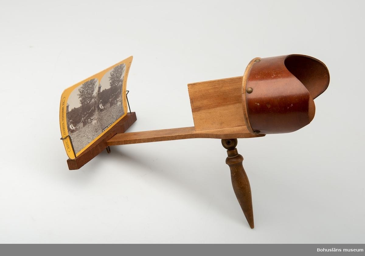 """Stereoskop med ögonskydd i trä, uppfällbart handtag i svarvat trä och med skjutbar bildhållare, UM027506:001. 37 tillhörande sv/v fotografier  - med dubblerade bilder - på kraftig kartong med olika motiv, humoristiska, sedelärande, topografiska eller upplysande. Påtryckt text eller text i relief. Format: 175 x 89 mm enligt följande: 5 st Popular Series  - UM027506:002-006 8 st """"International view Co., Photographers and Publishers,  Home Office and Works, Decatour, Illinois, USA """" - UM027506:007-014 1 st """" International view Co, Decatour, Illinois, USA""""  - UM027506:015 1 st """"GUST. A. JOHNSON. CLEARFIELD, PA. Series Comic and Groups."""" - UM027506:016 17 st """"GUST. A. JOHNSON, WINBURNE. PA. Series C. Comic and Gropus."""" - UM027506:017 -033 5 st """"GUST. A. JOHNSON, WINBURNE. PA. Series A. Sweden samt Series B, Unites States."""" - UM027506:034-038"""