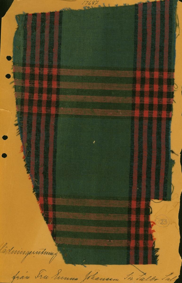 Anmärkningar: Vävnadsprov Olga Anderzons samling. Klänningsrutning, Fru Emma Johansson, Sör Salbo Salbohed, Västerfärnebo sn. Vävprov av halvylle i  tuskaft, rutigt. Varpen av bomull och inslaget av ull är randade lika men i olika färger. Varpen är i blått, rött och svart, inslaget i grönt, svart och rött. L. 1580 1860 Br. 2880 3000