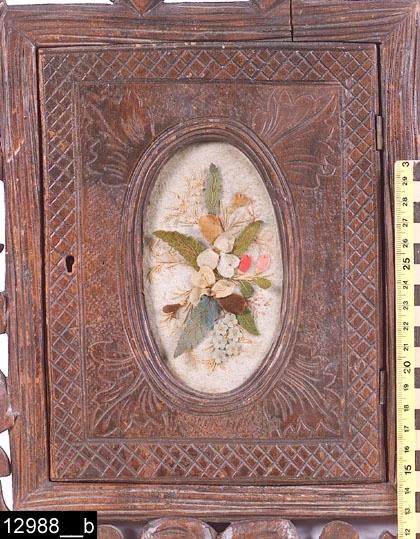 Anmärkningar: Skåp, sannolikt cigarr- eller tobaksskåp, mahogny, omkring 1900.  Applicerad, skuren och genombruten ram runt själva skåpet. Längst upp på ramen finns skurna korslagda cigarrer (bild 12988__e), i övrigt består dekoren i ramen av blommor och blad. Enkeldörr med oval spegel. I spegeln filtapplikationer med broderier (bild 12988__b). Kanten runt spegeln är profilerad. I varje hörn runt spegeln finns skurna blad (4st). Längs dörrens kanter skuret rutnätsmönster. Dörren omramas av profilerade kanter. Invändigt är skåpet indelat i fyra fack (bild 12988__c) och på insidan av dörren finns en läderbit som håller upp tygapplikationen på utsidan samt ett lås i järn (bild 12988__d). Insidan av dörren är ådringsmålad. Baktill två upphängningsanordningar i järn (bild 12988__f). H:540 Br:335 Dj:130  Tillstånd: Nyckel saknas. Gamla, eventuellt ursprungliga, lagningar på baksidan (bild 12988__f). Skåpet har invändigt en stark doft av tjära och gammal tobak (Access anm. 2006). Skåpet är betsat eller på något annat sätt ytbehandlat vilket ger det en glansig yta. Ett jugendbeslag i koppar föreställande en fladdermus ligger i skåpet. Osäkert om den tillhör skåpet (bild 12988__g).  Historik: Gåva från Hakonbolaget.