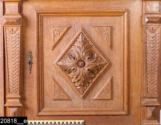 Anmärkningar: Buffé, tvådelad, nyrenässans, omkring 1900.  Överdel: Framskjutande profilerat rakt krön med dekorerad gavel upptill (bild 20818__b). Gaveln består av en fronton som överst har en svarvad knopp stående på en rektangulär platta och ett diamantsnitt. Under frontonen finns ett centralt parti med diamantsnitt och voluter och två halvkolonner. Partiet flankeras av skurna och kontursågade delar. Dekorerad fris med olika ornament under det framskjutande krönet. Spegelförsedd enkeldörr med gerade och profilerade lister samt en nyckelskylt i mässing. I spegeln finns skurna delar; en bevingad figur omgiven av druv- och fruktklasar, ett lejon, akantusar och en arkitektonisk rundbåge i bakgrunden (bild 20818__c). Joniska kolonner med skurna ornament i renässansstil på de nedre delarna. Invändigt två hyllplan och ett lås i järn. På båda sidor om dörren finns identiska avsatser (bild 20818__d). Längst upp på avsatserna finns skurna och profilsågade delar samt urnor med godronner, vilka står på varsitt krön som är närapå identiska med det stora krönet (beskrivet ovan). Inne i avsatserna finns vardera ett hyllplan och nedanför dem balustrader som fortsätter på sidorna. Där balustraderna möts i vinkel är diamantsnitt placerade. Från diamantsnitten leder kolonner rakt upp. Dessa har godronner, kannelyrer och skurna blad. Avsatserna vilar på rikt kontursvarvade balustrar med godronner. Mellan balustrarna sticker två konsoler ut som bär upp överskåpet. Konsolerna är profilsågade och har en skuren ornamental bandfläta. Bakstyckets framsida är försett med sju rektangulära speglar med gerade och profilerade lister samt pilasterformade avslut med kannelyrer på båda sidor. H:1580 Br:1655 Dj:685  Underdel: Framskjutande skänkskiva. Två kannelerade draglådor med vardera ett handtag i mässing. Handtagen är försedda med rik ornamentik och maskaroner (bild 20818__f). Lås i järn i båda lådor. Spegelförsedda pardörrar med gerade och profilerade lister. I speglarna finns upphöjda romb