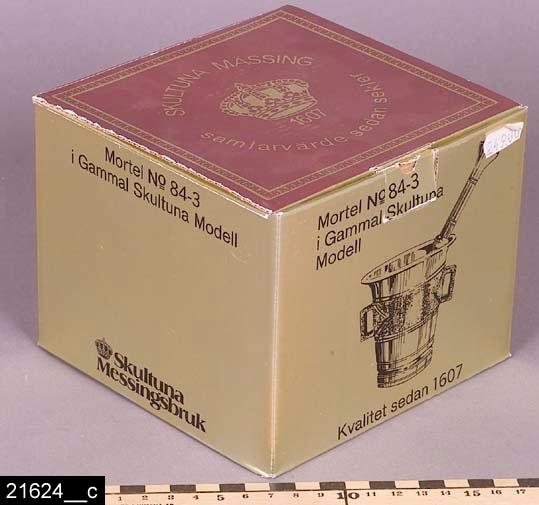 """Anmärkningar: Mortel, tillverkad 1981.  Rund nedåt avsmalnande mortel med genombrutna öron på sidorna. Tillhörande stöt som är 150 mm lång (som har invnr. 21625). Parallella dekorationslinjer löper runt morteln och vid öronen rombformad dekor. På mittpartiet är gjutytan lämnad rå. I botten finns stämplarna """"SKULTUNA 1607 G10 No3"""" (bild 21624__b). Till morteln hör en orginalförpackning (bild 21624__c). 1977 införde Skultuna Bruk årsstämplar (samma som gäller för guld). G10 står för 1981. Enligt en broschyr, utgiven av museet 2007 och benämnd """"Skultunastämplar 1800-2000"""", började den typ av stämpel som finns på föremålet användas 1922. Den användes fortfarande år 2007. H:75 D:75  Tillstånd: Nyskick.  Historik: Inköpt för 153 kronor plus moms 1983."""