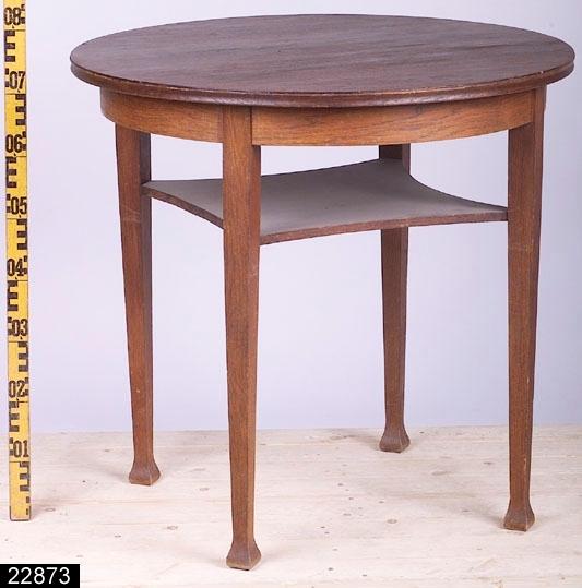 """Anmärkningar: Bord, sen jugend, omkring 1920.  Rund bordsskiva med kälad kant. Fyra nedåt avsmalnande ben med svagt konformiga fotavslutningar. Mellan benen finns en hylla. H:765 Diam:795  Hela bordet är av massiv ek utom sargen som har blindträ av furu och är fanerad med ek. Enligt en äldre registrering (gjord av MLO 1985 då bordet köptes in) är bordet avsett för blommor.  Historik: Inköpt till utställningen """" Bostad"""" hösten 1985 från Fastberg & Söner, Vångsta, Västerås för 35 kronor."""