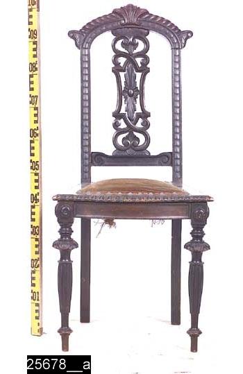 Anmärkningar: Stol, nyrenässans, svärtad, omkring 1900.  Överstycke med skurna dekorer (jämför bild 25670__c); i mitten en snäcka, på sidorna om denna spiralformer och längst ut på ändarna voluter. Under dessa dekorationer finns en skuren stiliserad bandfläta som fortsätter längs båda bakstolpar i höjd t.o.m. sitsen. Genombruten rygg med skurna dekorer på ryggbrickan, bl.a. ett blad i mitten (jämför bild 25670__e). Under denna dekor finns en horisontal ryggslå med skurna voluter. Sköldformad träsits med stoppad del som är försett med ett brunt tyg (bild 25678__b). Detta är fäst i stolen med dimantsnittsformade tännlikor i mässing. Sitsens kanter är försedda med skuren dekor (dock ej baktill, jämför bild 25670__d). Framsarg och sidosarger har rektangulära kälningar. Bakbenen sticker ut från stolen (jämför bild 25670__b). Två anfanger framtill med runda dekorer framtill och på sidorna (jämför bild 25670__f). Profilsvarvade framben med palmettliknande skuren dekor. Halvkolonnliknande dekor under kragarna. Därefter rundningar och smala runda fotavslutningar. H:1025 Br:465 Dj:530  Se även invnr. 10451. Invnr. 25678 ingick ursprungligen i 10451 och har splittrats av Sesam. Se även invnr. 25668-25677.  Tillstånd: Stoppningen undertill är trasig (bild 25678__c).  Historik: Gåva av Nils Nygren, Västerås.