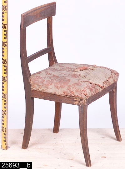 Anmärkningar: Stol, Karl Johan, 1800-talets första hälft.  Svagt konvext överstycke. S-svängda bakstolpar (bild 25693__b). Genombruten rygg med en ryggslå. Överstycket och ryggslån är profilerade. Stoppad sits med blommigt tyg (bild 25693__c). Fyra utåtsvängda ben (bild 25693__b). H:810 Br:460 Dj:460  Hela stolen är av ljust lövträ utom framsargen och bakstolparna som är av furu. Hela stolen är mörkröd, överstycket bär spår av naturligt slitage.  Invnr. 25693 ingick ursprungligen i invnr. 2710. Enligt kortkatalogen saknas fyra stolar (ursprungligen bestod invnr. 2710 av 6 poster). De saknade stolarna finns ej i 2003 års inventeringsförteckning över Vallby. En post har splittrats av projektet Sesam och har fått invnr. 25693.  Tillstånd: Stolen är ranglig och maskstungen. Överstycket sitter löst. Stoppningen och tyget är skadade.  Historik: Gåva av Holmberg, Västerås 1923.