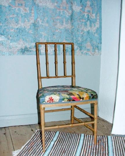 """Anmärkningar: Stol i bambuimitation. Stolen har spjälrygg med tre spjälor i profilsvarvat trä. Ben av profilsvarvat trä, med en tvärslå fram och bak, två tvärslåar på stolens sidor. Stolssitsen klädd med storblommigt tyg. Tyget har blå bakgrund med mönster av stora vita och rosaröda blommor, trädgrenar och blad i gröna och bruna toner samt fåglar i gröna och bruna färger. Stolen är ommålad med ljust brungrön färg. Under färglagret syns ett lager med röd brun färg. Märkt under med """" 438b""""."""