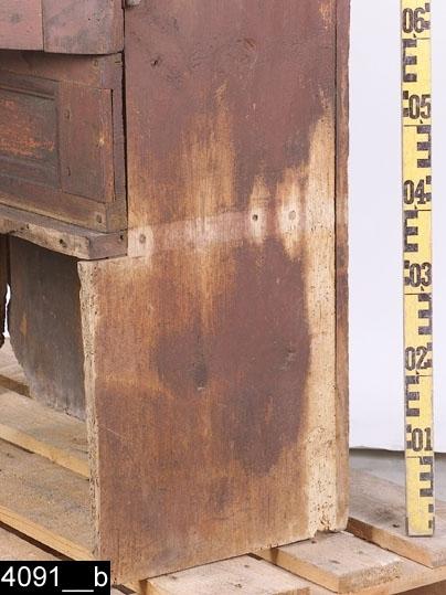 Anmärkningar: Skåp på hög fot, s.k. matskåp, rödbrunt, omkring 1800.  Framskjutande profilerat krön. Tre rektangulära nedbottningar under krönet samt en lång rektangulär nedbottning under dörrarna. Pardörrar med sneda speglar. Färgen på höger sida av den vänstra dörren bär spår av naturligt slitage. Dörrspeglarna har underliggande grön färg. Profilerade gerade lister kring ramar, speglar och nedbottningar. Hög öppen fot. Skedhylla samt två hyllplan invändigt. H:1540 Br:850 Dj:380  Matskåp av den här typen är mest förknippat med Dalarna. Troligen har det kommit hit på samma sätt som skänkskåpen, d.v.s. genom en marknad. Matskåpet placerades längs med stugans väggfasta långbänk. Stundom kunde matskåpet även vara integrerat med detsamma. Möjligen har detta varit fallet med museets matskåp då högra sidan bär spår av att ha hört samman med en bänk (bild 4091__b). Litt: Sigurd Erixon, Foklig möbelkultur i svenska bygder, 1938. s72-73 och s120)  Tillstånd: En inläggning saknas nedanför krönet (bild 4091__a). Lås saknas.  Historik: Köpt på auktion för 3 kronor av fru Ida Nygren 1925, Västerås.  Negativnummer X-1605.