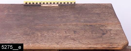 Anmärkningar: Skåpbord, möjligen ett kryddskåp (detta enligt liggaren), rödbrunt, 1700-tal.  Framskjutande bänkskiva med avfasade hörn. Bänkskivan bär spår av naturligt slitage (bild 5275__e). Spegelförsedda pardörrar med gerade och profilerade lister. Nyckelskylt i järn på vänster dörr. Invändigt åtta draglådor av varierande storlek med svarvade knoppar (bild 5275__b). Samtliga har gerade och profilerade lister. Invändigt ett lås i järn på höger dörr. Kontursågad nederdel (både på fronten och sidorna)) samt fyra fötter. H:730 Br:935 Dj:495  Tillstånd: Färgen är gammal, men är ej ursprunglig. De ursprungliga färgerna har bland annat varit blått och rött. Dessa har också varit väldigt klara (bild 5275__c-d). Lister saknas på samtliga lådfronter utom lådan i mitten och den till vänster om denna. En låda saknas och på en saknas knopp. Nyckel saknas. Nyckelskylt saknas på höger dörr. Skåpet lutar något bakåt p.g.a. att fötterna baktill är skadade.  Historik: Köpt för 10 kronor, 1926.